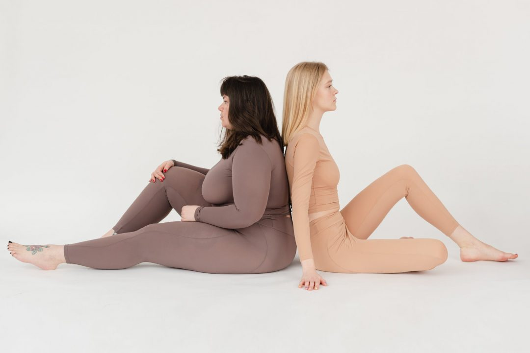 young slim and obese women sitting back to back in white studio